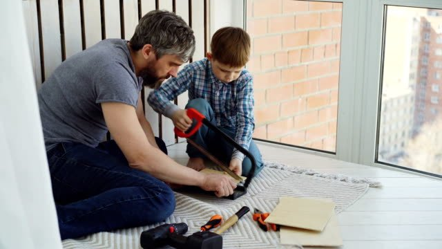 Little-boy-is-focused-on-sawing-piece-of-wood-with-hand-saw-with-his-father-helping-and-teaching-him-United-family-construction-work-and-childhood-concept-