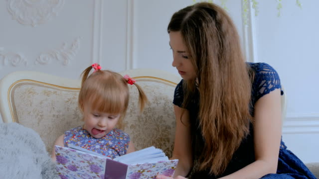 Young-mother-and-her-baby-daughter-looking-photobook