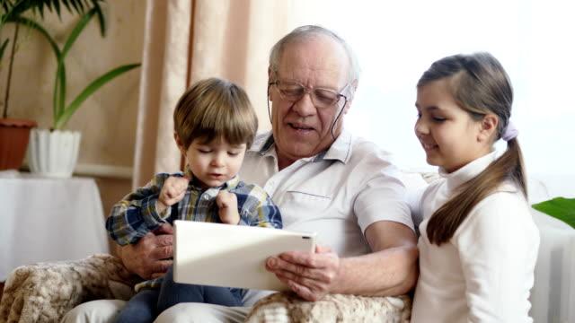 Abuelo-usando-un-Tablet-PC-con-nietos