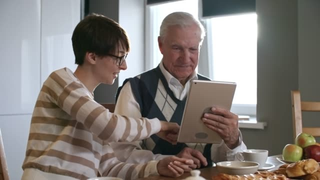 Granddaughter-Helping-Grandfather-with-Tablet