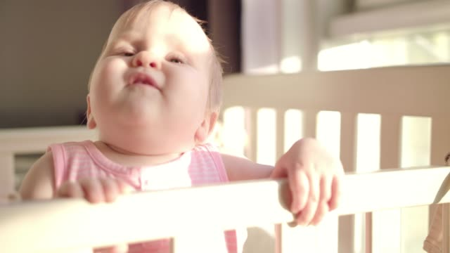 Beautiful-baby-standing-in-crib-Toddler-learning-to-stand-in-bed-at-home