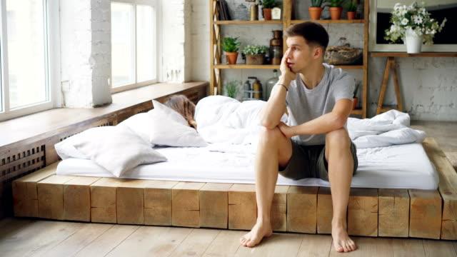 Hombre-triste-sentado-en-la-cama-después-de-pelea-con-su-esposa-tocando-su-cara-y-mirando-a-la-ventana-mientras-su-esposa-está-acostado-en-la-cama-con-la-espalda-a-él-Concepto-de-crisis-y-la-gente-familia-