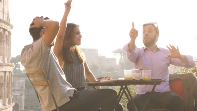 Three-young-friends-having-fun-laughing-telling-stories-and-jokes-with-exagerated-gestures-sitting-at-bar-restaurant-table-in-front-of-colosseum-in-rome-at-sunset