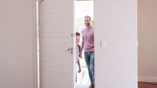 Family-Opening-Door-And-Walking-In-Empty-Lounge-Of-New-Home