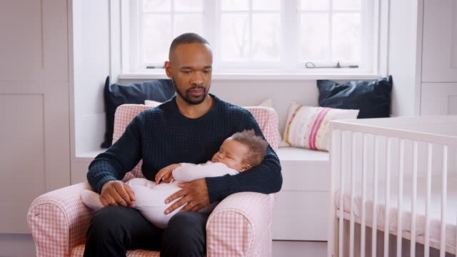 Stressed-New-Father-Sitting-In-Chair-Holding-Sleeping-Baby-Girl-In-Nursery-At-Home