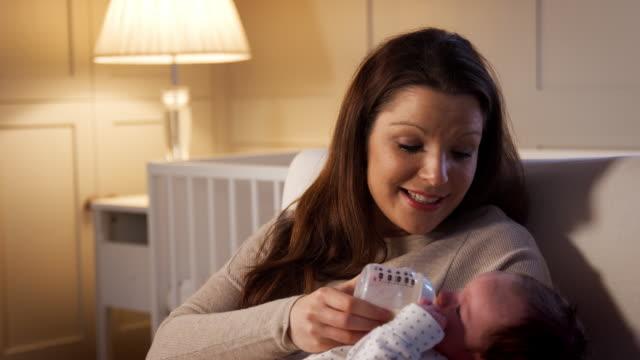 Mutter-im-Kindergarten-neugeborenes-Baby-aus-der-Flasche-füttern