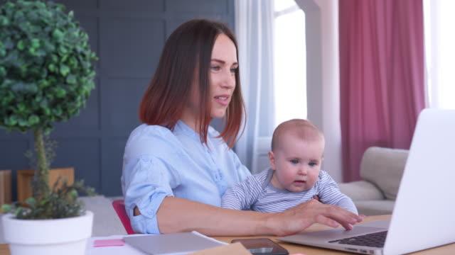 Feliz-madre-con-la-niña-mientras-trabajaba-en-su-casa