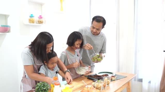 Familia-feliz-asiáticos-cocineros-en-la-cocina-en-casa