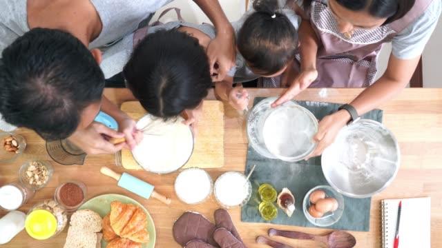 Vista-superior-feliz-familia-cocineros-en-la-cocina-en-casa