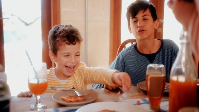 Joven-que-se-divierte-comiendo-saludable-desayuno-con-la-familia