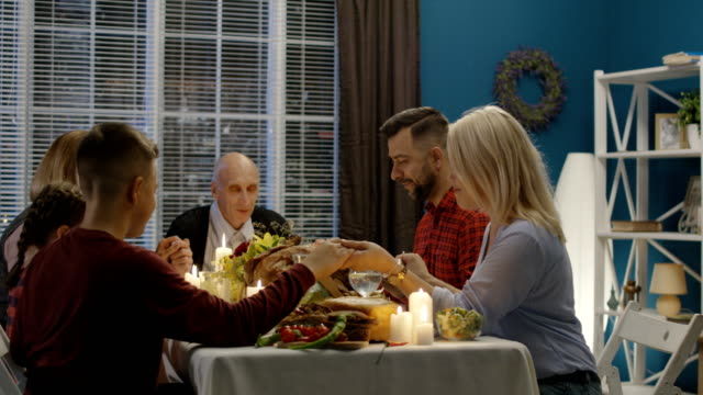 Family-offering-prayers-before-Thanksgiving-meal