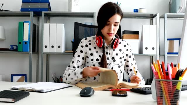 mujer-con-auriculares-rojo-en-hombros-cierre-el-libro-y-que-se-inclinan-hacia-atrás
