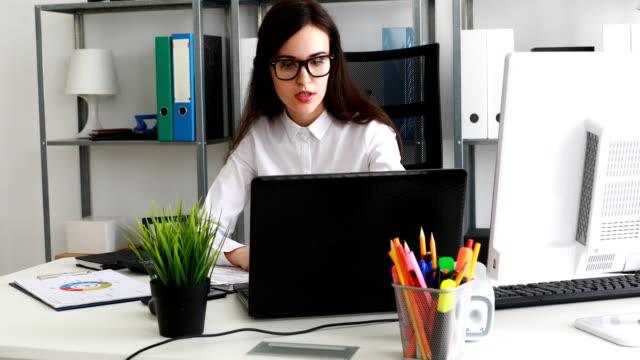 empresaria-en-gafas-negras-trabajando-en-ordenador-portátil-en-la-oficina-moderna