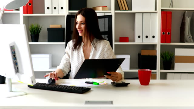 brunette-businesswoman-working-with-documents-in-light-office