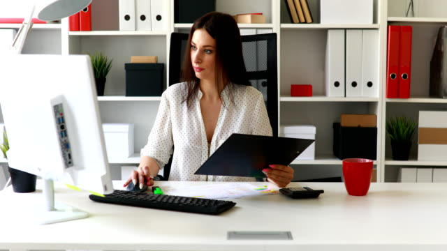 businesswoman-working-at-computer-in-light-office-and-looking-at-kamera