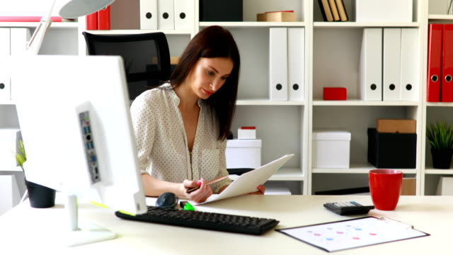 businesswoman-sitting-in-office-chair-and-looking-in-documents