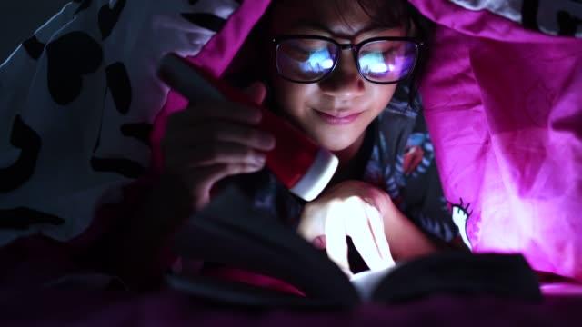 Girl-holding-flashlight-while-reading-books-blanket-at-home