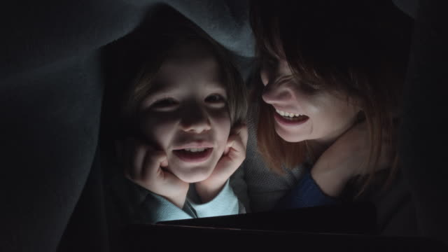 4k-Shot-of-Child-and-Mom-Looking-on-Tablet-under-Blanket