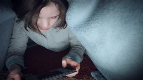 4k-Shot-of-Child-under-Blanket-Looking-on-Tablet