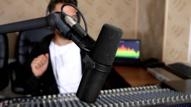 radio-presenter-in-earphones-into-front-of-audio-console-on-radio-studio-in-unfocused-background