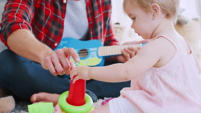 Young-dad-playing-with-his-toddler-daughter-at-home-close-up