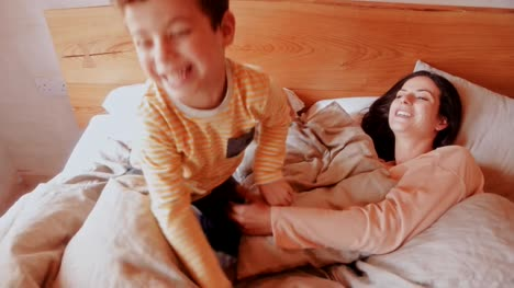 Mother-and-son-having-fun-in-bed-in-the-morning