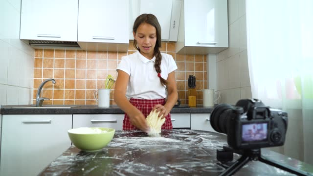 Young-vlogger-recording-video-content-for-food-blog-kneading-dough
