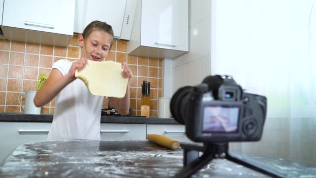 Young-vlogger-recording-video-content-for-food-blog-rolling-dough-with-rolling-pin