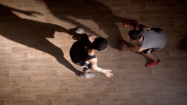 Topshot-zwei-Basketball-Spieler-einander-zugewandt-auf-Platz-und-versucht-die-Kugel-nehmen