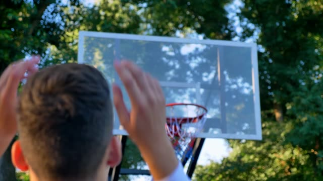 Back-of-man-jumping-and-throwing-basketball-ball-hits-ring-passing-through-hoop-playing-in-park-daytime