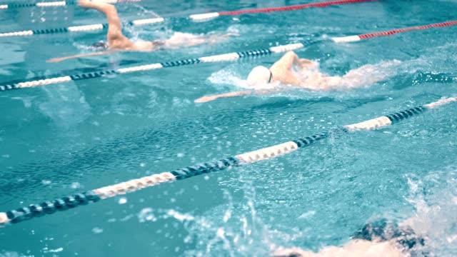 Nadadores-de-alto-ángulo-tres-teniendo-competencia-en-piscina-tracking-shot