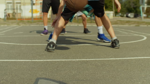 Young-man-on-basketball-court-dribbling-with-ball