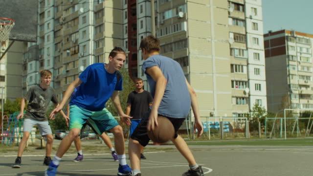 Streetball-adolescente-jugador-botando-y-rebotando-la-pelota-en-el-piso-pasando-a-su-compañero-de-equipo-jugando-al-Juego-de-baloncesto-en-la-calle-Protector-de-baloncesto-robar-una-pelota-y-correr-en-ayuno-