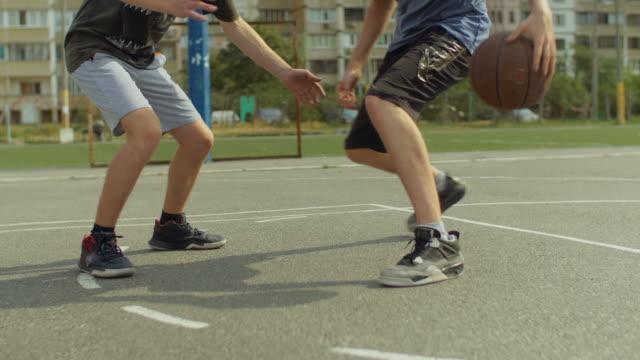 Junger-Mann-am-Basketballplatz-mit-Ball-dribbeln