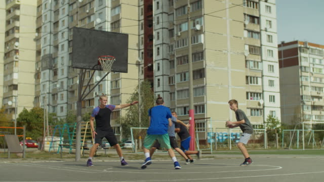 Active-teeange-friends-playing-streetball-outdoors