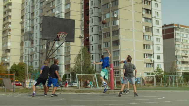 Streetball-players-playing-basketball-on-court
