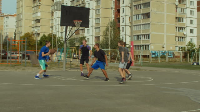 Active-teenagers-playing-streetball-game-outdoors
