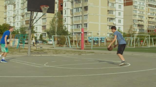 Teenagers-training-basketball-skills-on-outdoor-court