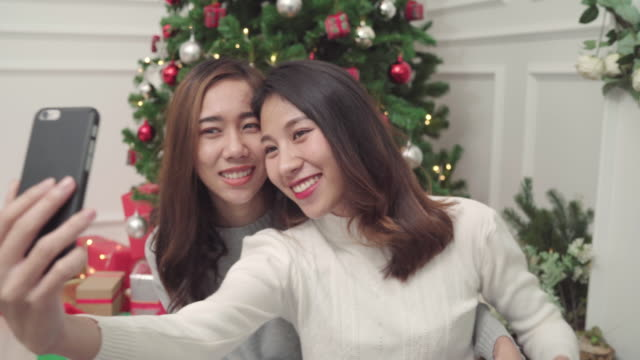 Group-of-cheerful-happy-young-Asian-woman-using-smartphone-selfie-with-christmas-tree-decorate-her-living-room-at-home-in-Christmas-Festival-Lifestyle-women-celebrate-Christmas-and-New-year-concept-