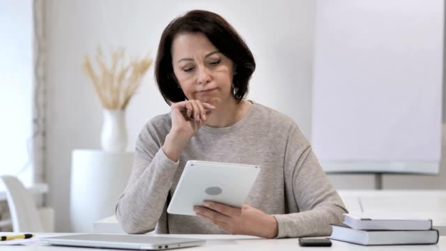 Pensativo-antigua-Senior-mujer-pensando-mientras-usando-la-tableta