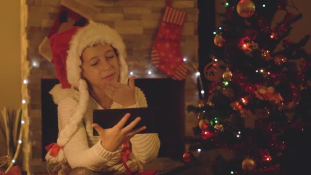Niña-feliz-uso-de-tableta-en-una-video-llamada-en-Navidad-en-el-salón-decorado-con-árboles-y-chimenea-