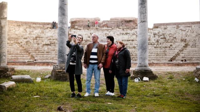 Hombre-senior-feliz-y-las-mujeres-con-niña-agitando-en-video-chat-con-familiares-cerca-de-antiguas-ruinas-del-anfiteatro-en-Ostia-Italia-