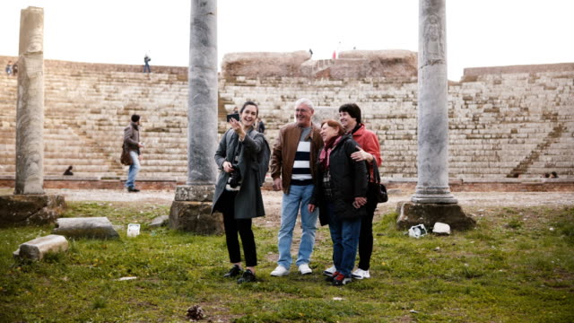 Smiling-senior-family-and-young-woman-tourists-waving-on-video-call-to-family-at-old-amphitheater-ruins-in-Ostia-Italy-