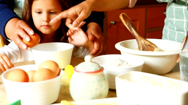 Girl-preparing-food-with-family-in-kitchen-4k