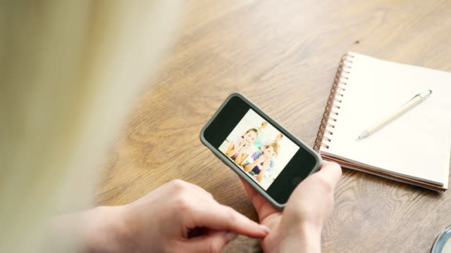 Attractive-Blond-Woman-Swiping-Through-Family-Album-On-Smart-Phone