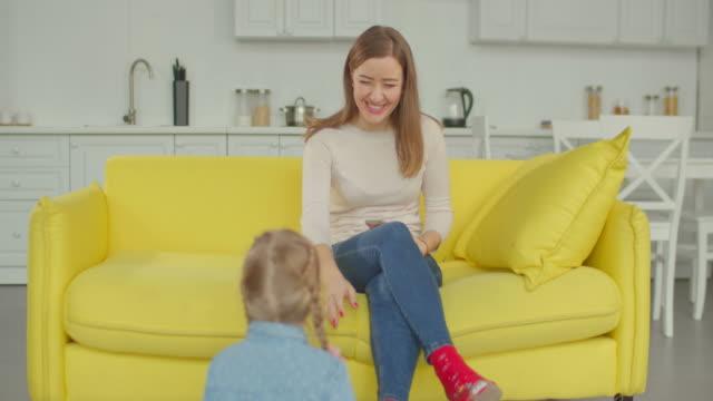 Joyful-little-girl-needs-attention-of-her-busy-mum