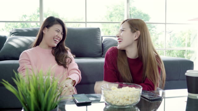 Asian-women-using-smartphone-and-eating-popcorn-in-living-room-at-home-group-of-roommate-friend-enjoy-funny-moment-while-lying-on-the-sofa-Lifestyle-women-relax-at-home-concept-
