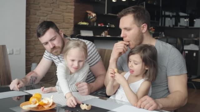 Schöne-Familie-mit-gleichen-Geschlechts-Eltern-samt-Teilen-einer-Mandarine