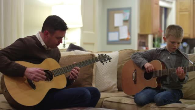 Padre-e-hijo-practicando-en-sus-guitarras-en-la-sala-de-estar