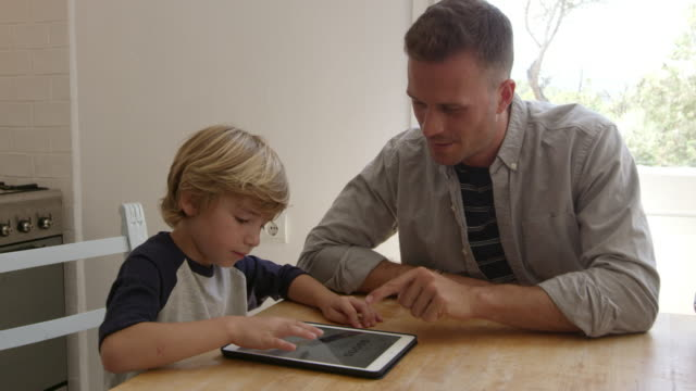 Father-and-son-using-tablet-computer-at-the-kitchen-table-shot-on-R3D